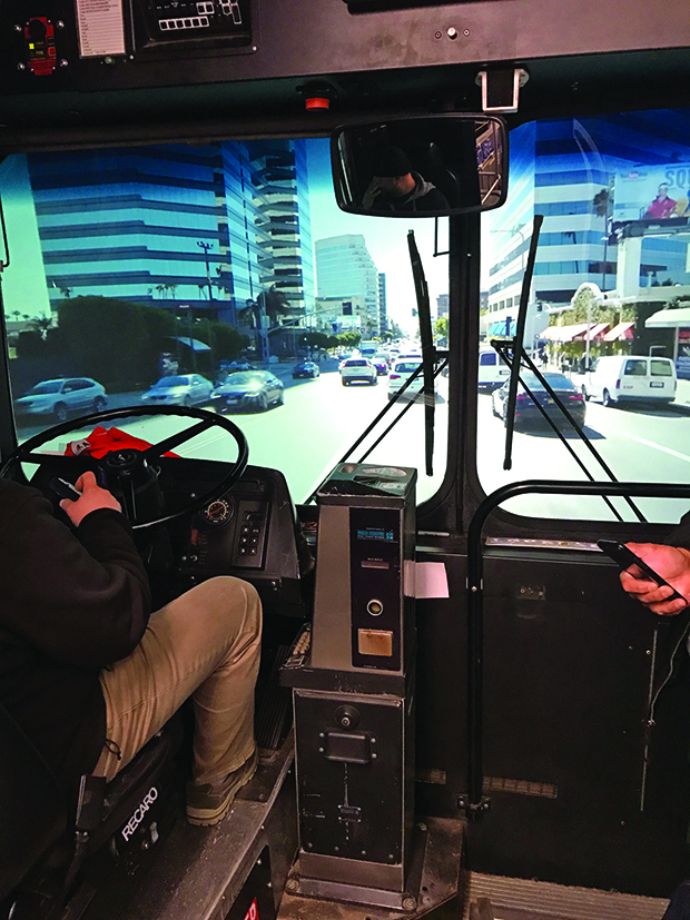 The camera's view of projected  driving inside the bus for an episode of Curb Your Enthusiasm.